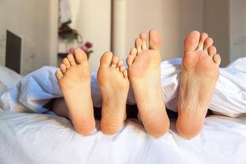 Close-up of bare feet in bed at home