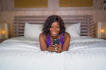 happy black African American woman sitting on bed using internet mobile phone smiling cheerful and relaxed networking online business or social media at home