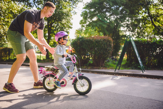 father teaches little toddler daughter to ride a bike in the park