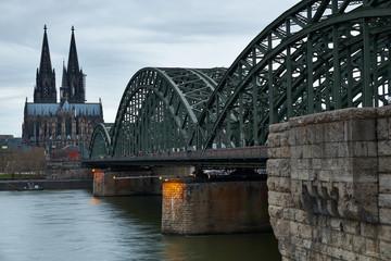 Kölner Dom und Hohenzollernbrücke kurz vor Sonnenuntergang bei bewölktem Himmel