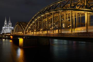 Hohenzollernbrücke und Kölner Dom am Rhein bei Nacht, Ein Zug fährt in den Kölner Hauptbahnhof ein