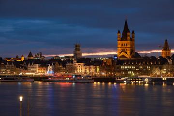 Panorama Köln mit der Groß St. Matrins Kirche und der Kölner Altstadt mit Blick über den Rhein,  am Horizont die letzten Sonnenstrahlen und Königsblauer Himmel