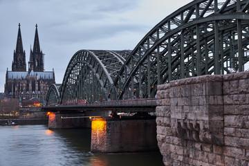 Der berühmte Blick auf die Wahrzeichen von Köln bei Tag. Über die Hohenzollernbrücke fahren täglich hunderte Züge und tausende Menschen, während sie den Ausblick auf das Kölner Panorama genießen.