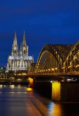 Kölner Dom und Hohenzollernbrücke bei Nacht während der blauen Stunde im Hochformat.