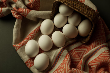 White chicken eggs, on decorative fabric, and in a beautiful basket, preparation for Easter