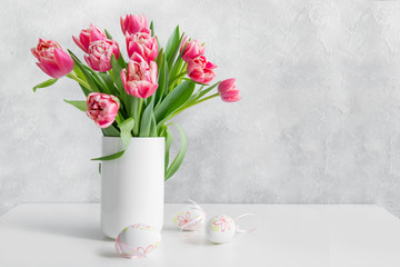 Bouquet of red tulip in vase on white vintage table. Space for text.