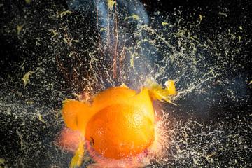 Orange burst into pieces on black background