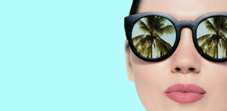Portrait close up of a pretty woman with reflection of palms in sunglasses  on a bright background