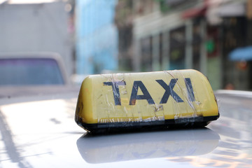 Taxi light sign or cab sign in yellow color with black text and tied with transparent tape on the car roof at the street blurred background.
