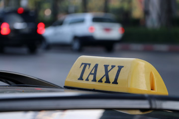 Taxi light sign or cab sign in yellow color with black text on the car roof at the street blurred background