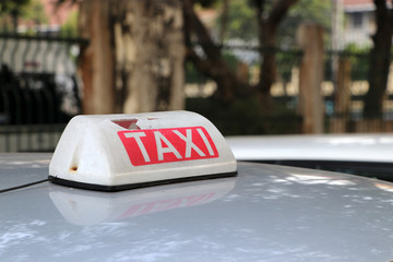 Broken Taxi light sign or cab sign in white and red color with white text on the car roof at the street blurred background.