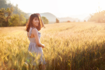 Beautiful and happy asian woman enjoying life in barley field at sunset.
