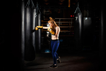 Blonde in boxing gloves trains near black punching bag.