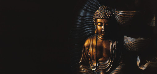 Poster Boeddha Golden Gautama Buddha statue with a black background.