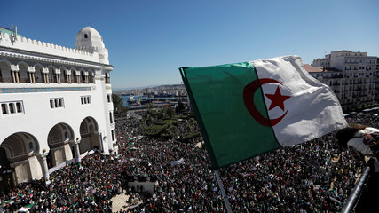 An Algerian flag flutters as people gather during a protest over President Abdelaziz Bouteflika's decision to postpone elections and extend his fourth term in office, in Algiers