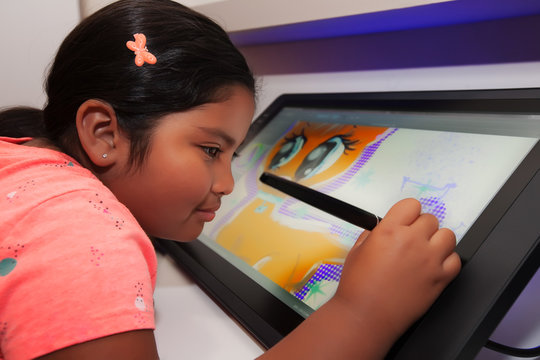 Young girl using a digital pen and drawing tablet to be creative and to make digital art in a classroom.