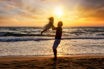 Silhouette of a happy father on vacation holding his daughter in the air on the beach during sunset time