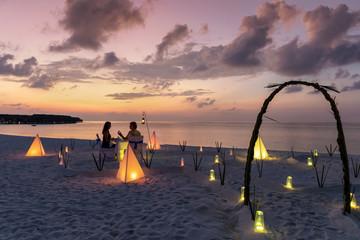 Paar in den Flitterwochen sitzt bei einem privatem Abendessen am Strand und genießt den Sonnenuntergang