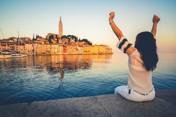 Woman traveler travels in a beautiful romantic old town of Rovinj in Croatia. Coastal city of Rovinj situated in Istria Peninsula east of Croatia Europe, it is famous travel destination of Croatia.