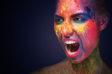 Screaming woman with unusual bright make-up on white