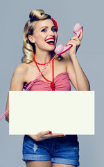 woman with phone and blank signboard, dressed in pin-up style