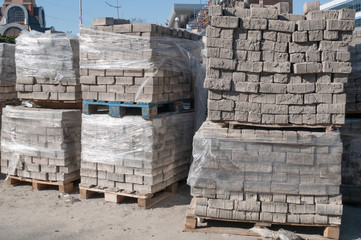 outdoor warehouse with lot of pallets full of bricks pavement stones