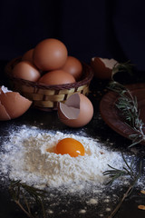 Horizontal view. Eggs, rosemary, flour and oatmeal lie on a clay tray