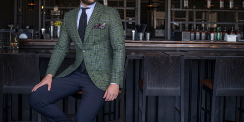 Man in expensive custom tailored suit with green jacket sitting and posing at bar