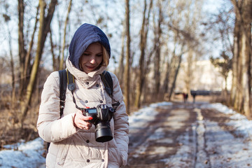 Woman with a camera on a walk in the woods in spring.