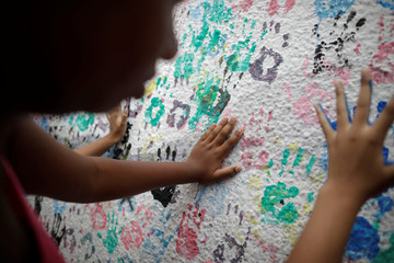 Students place their handprints on a wall at the Raul Brasil State School while paying tribute to victims of the shooting in the Raul Brasil school in Suzano