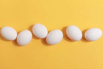 Set of white chicken eggs on a yellow background. Preparation for painting Easter eggs. Top view.