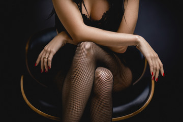 slim sexy woman in black stockings sits on a chair on a black background