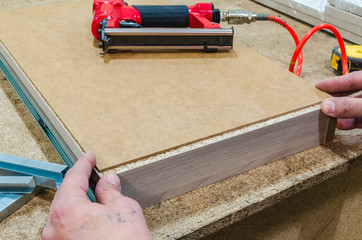 Red pneumatic stapler nails the bottom to the drawer