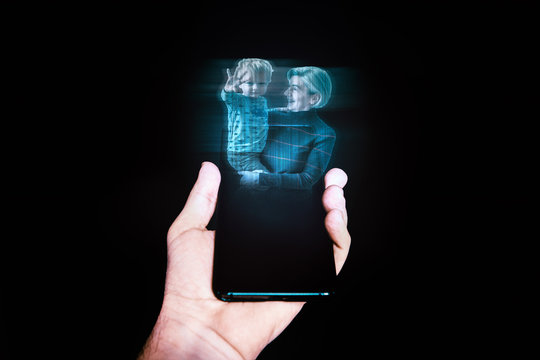 hologram of a child and grandmother displayed on a smartphone held by an hand.  future connectivity, next communication, family relationship concept
