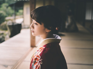 Thoughtful young woman in kimono standing outdoors
