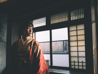 Thoughtful young woman in kimono standing indoors