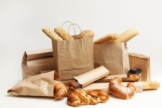 Different fresh bakery products in paper bags on white background
