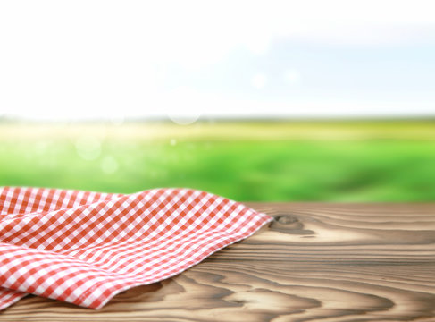Red picnic cloth on wooden table nature background.
