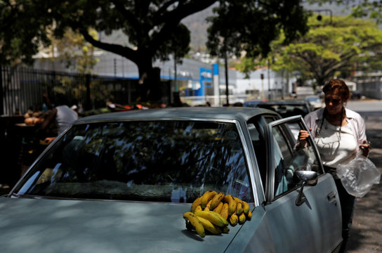 A handful of bananas is seen on top of a car after a woman bought them at a vegetable and fruit stall on the street in Caracas