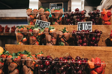 Cups of fresh strawberries, cherries and  strawberries dipped in milk chocolate on sale.