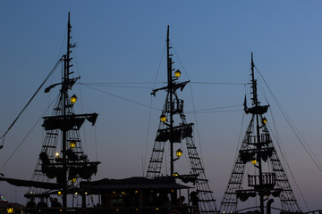 twilight medieval pirates ship silhouette soft focus shape with lantern illumination