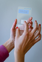 Woman hand holding transparent smartphone and touching a keyboard on screen. Social media, business, technology and people concept