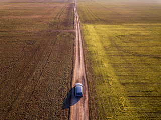 Aerial view of car driving by straight ground road through green fields on sunny blue sky copy space background. Drone photography. Wall mural