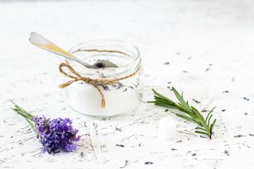 Glass jar with lavender sugar, fresh lavender on a light wooden background