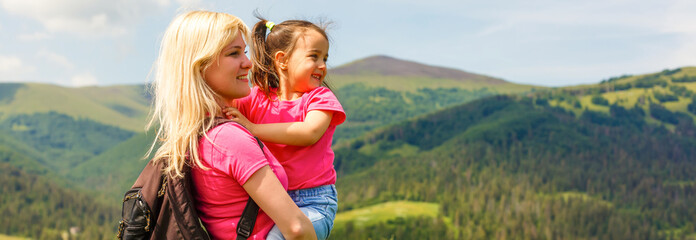 mother and little daugther hiking in mountains