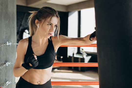 Female Punching a Boxing bag With Boxing Gloves at the gym. Concept about sport, fitness, martial arts and people