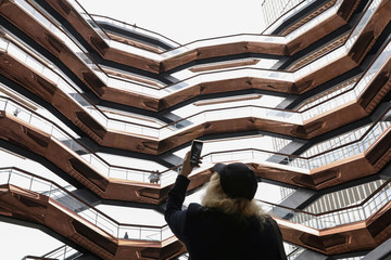 A woman photographs inside 'The Vessel,' a large public art sculpture made up of 155 flights of stairs, during the grand opening of the The Hudson Yards development in New York