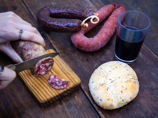 One person cutting an Iberian pork sausage on an old wooden board with an antique knife and rustic bread and a glass of red spanish wine