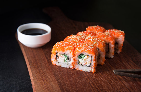 Sushi California Roll with crab meat, cucumber, masago and soy sauce on a wooden cutting board, black background, close-up