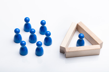 Figurine Pawn Separated By Wooden Blocks From Blue Figurines